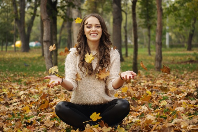 woman-tossing-leaves-in-yoga-pose